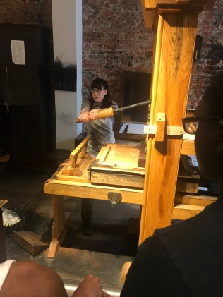 Worker using the printing equipment at the Franklin Print Shop